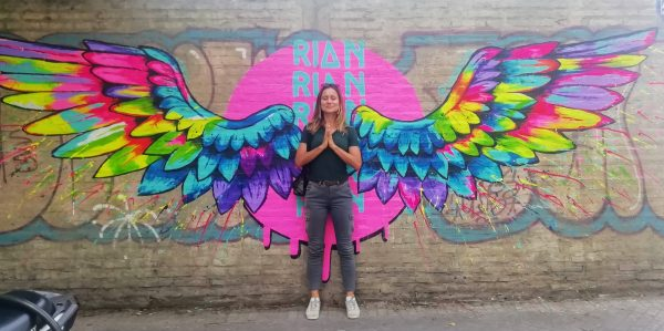 Girl with green top standing against the wall with painted wings